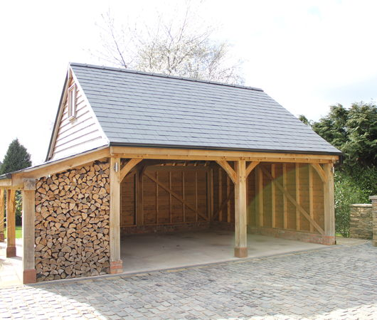 Radnor Oak's two bay oak garage with log store to one end.