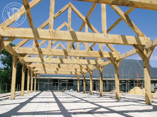 an oak frame taking shape in the summer sunshine